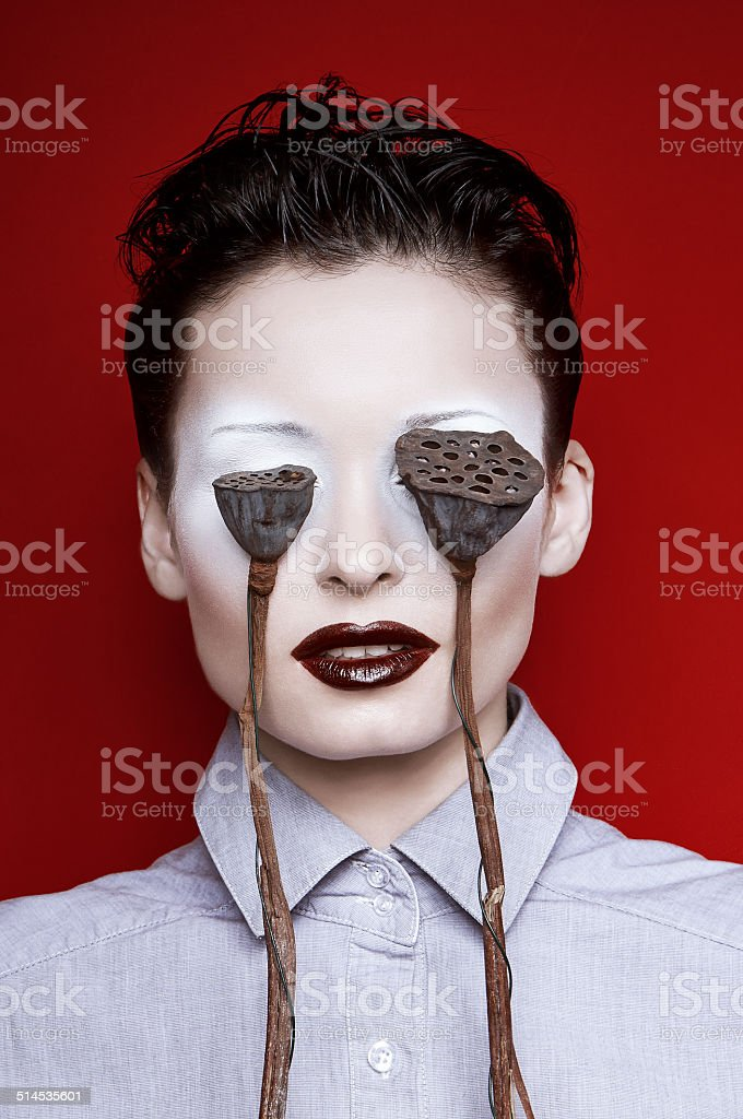 Girl with make-up and floral capsules before her eyes royalty-free stock photo