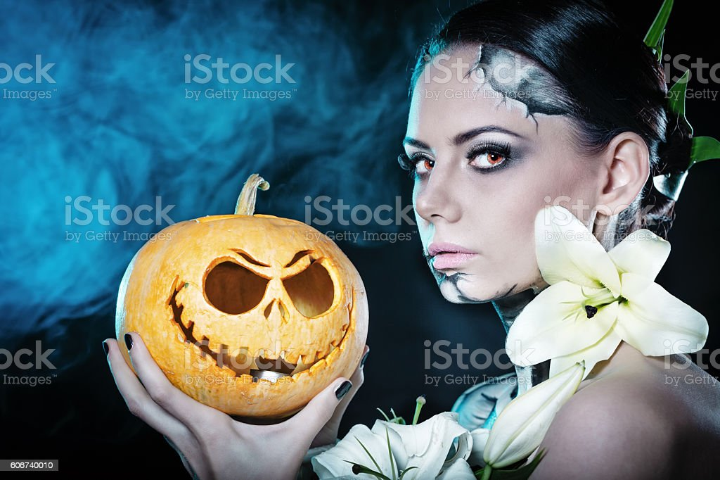 Girl with makeup for Halloween. Pumpkin stock photo