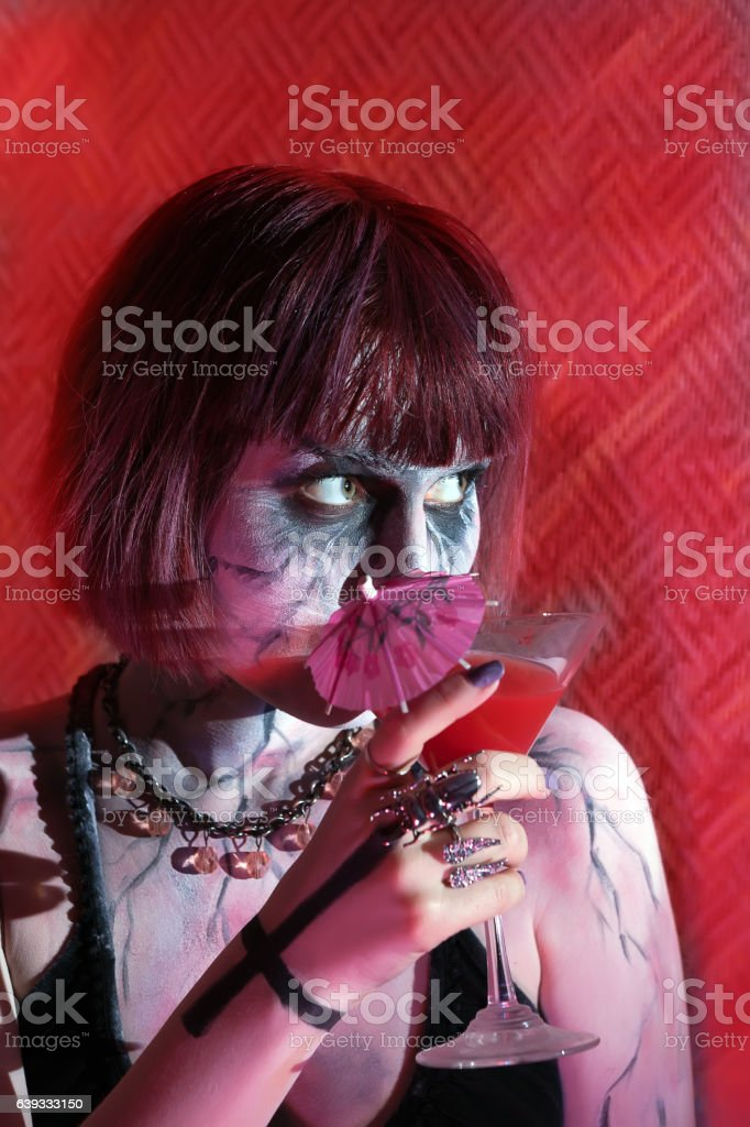 girl with makeup zombies drinking red cocktail stock photo
