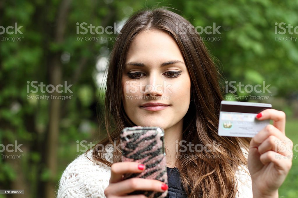 Beautiful girl using mobile phone and holding credit card in her hand