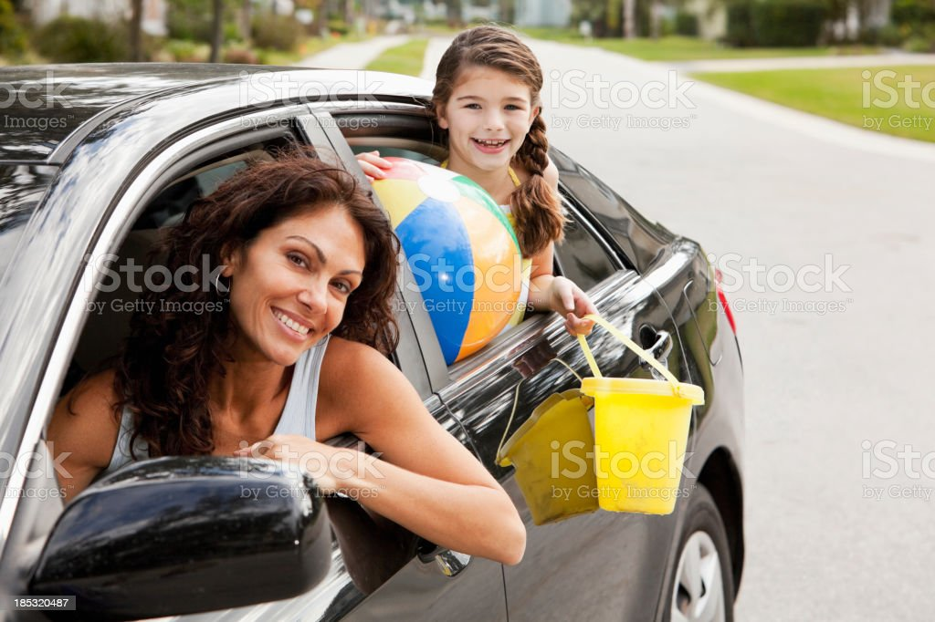 Girl with mother in car driving to beach stock photo