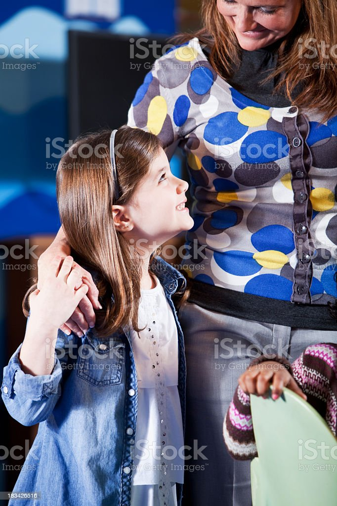 Girl with mother or teacher at school stock photo