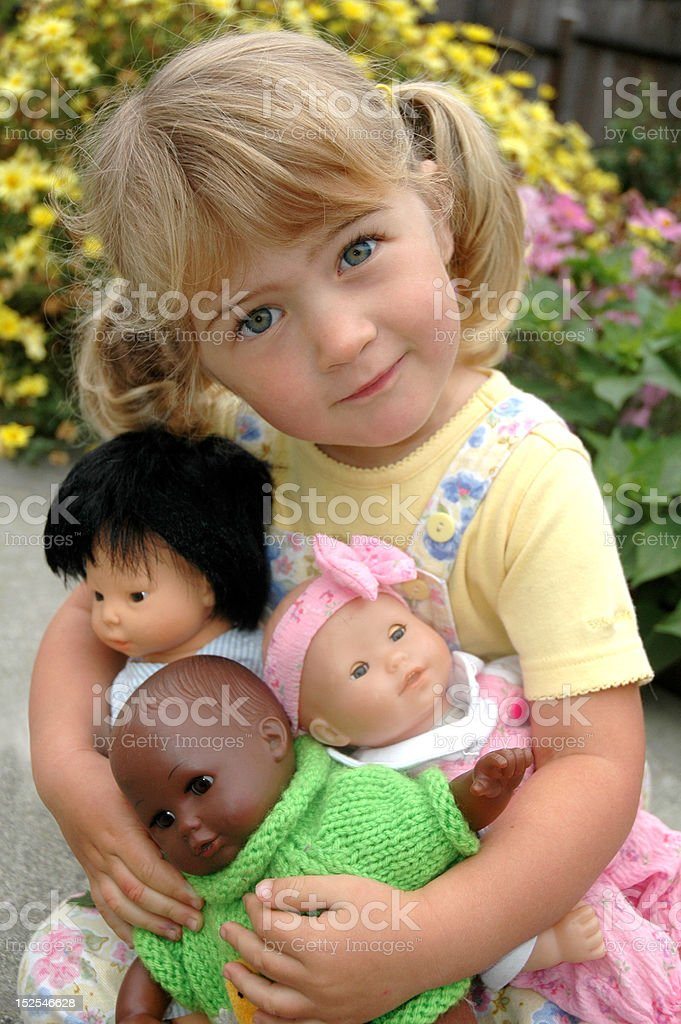 Girl with multi=ethnic dolls stock photo
