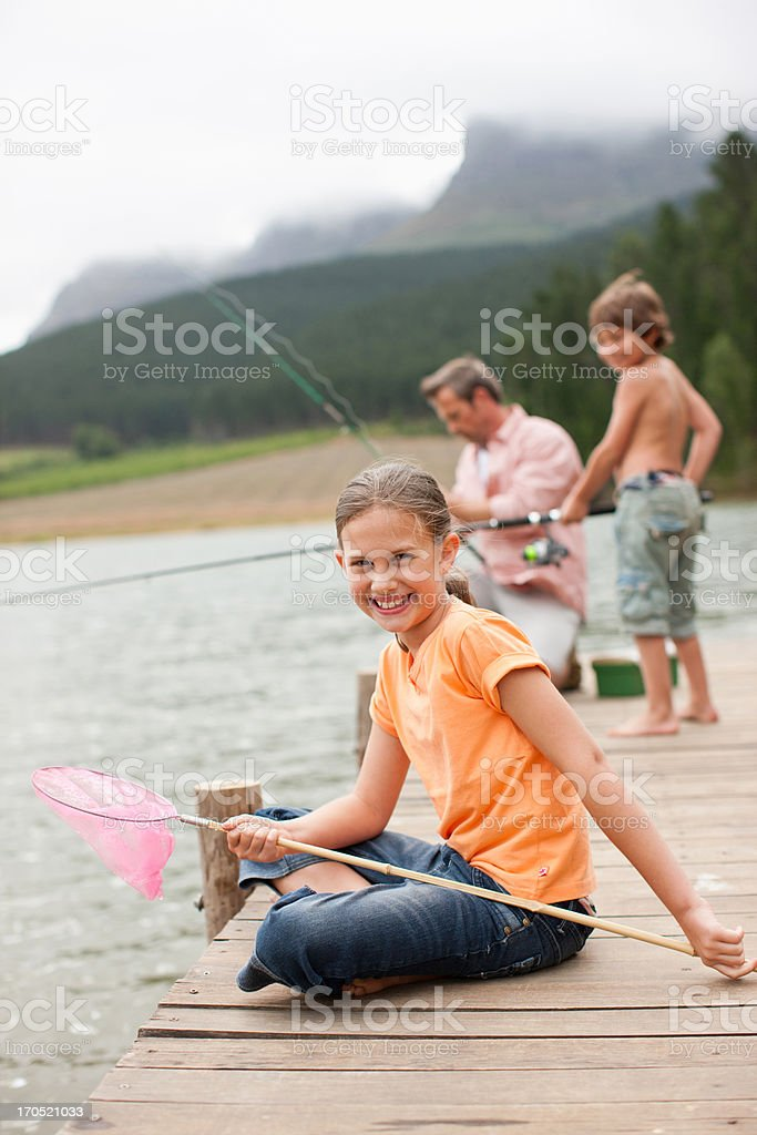Girl with net sitting on pier by lake royalty-free stock photo