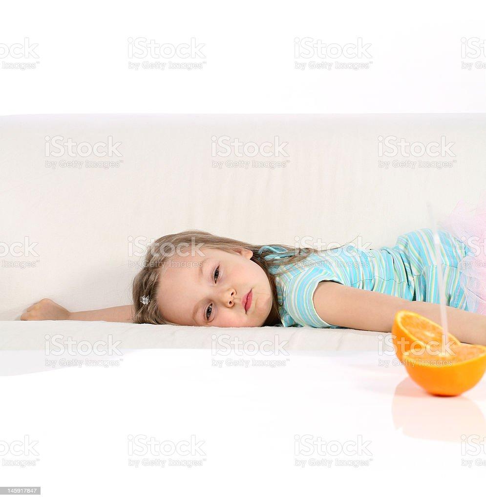 Girl with orange on a sofa royalty-free stock photo