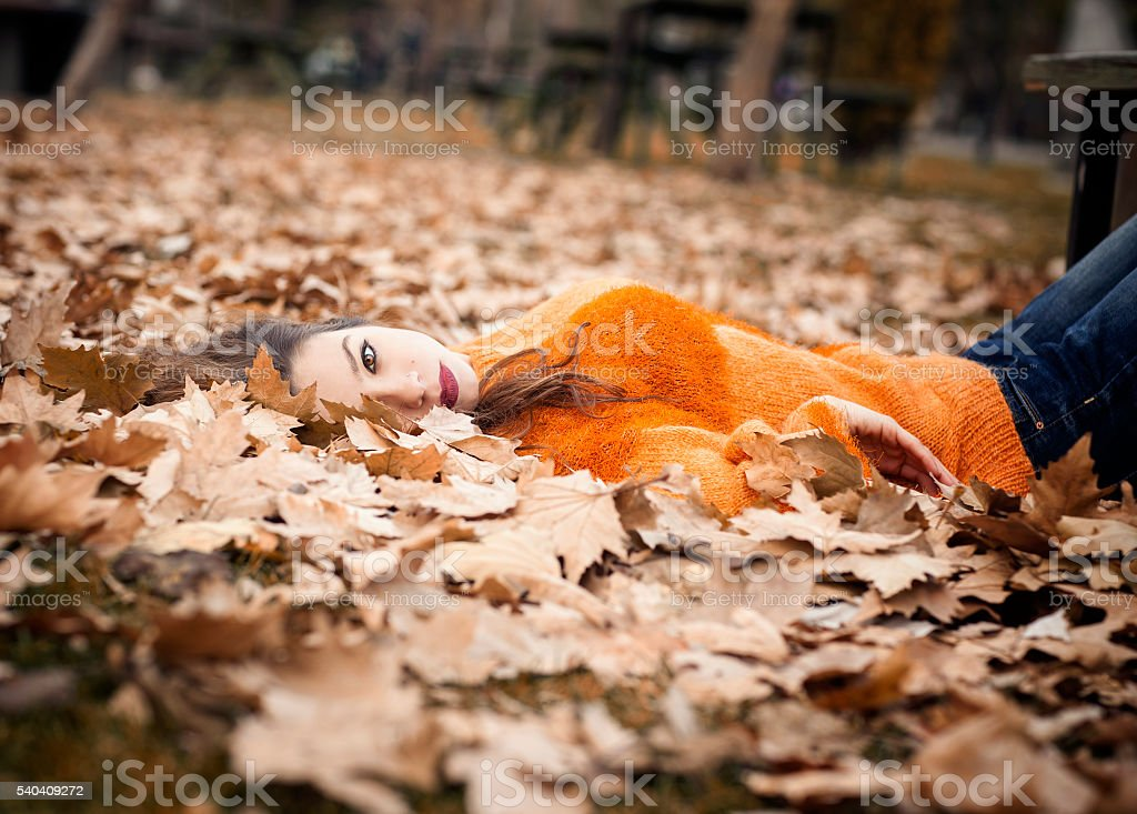 girl with orange sweater lying in autumn leaves. stock photo