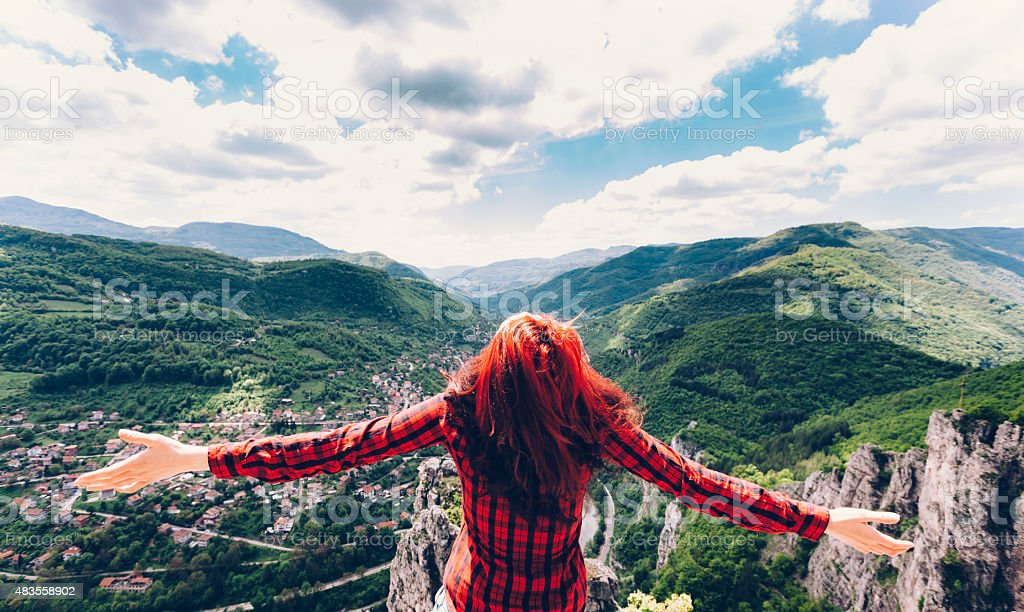 Girl with outstretched hands at the top of a mountain stock photo
