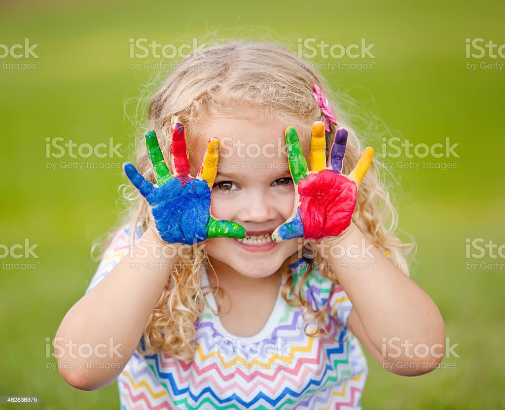 Girl With Painted Hands Outdoors stock photo