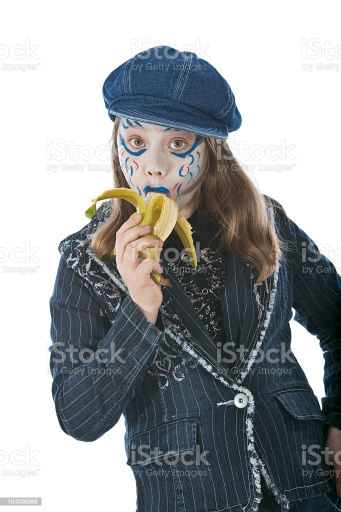 Girl with painting face eats the banana stock photo