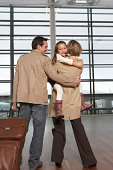 Girl (5-7) with parents in airport, being carried by mother, smiling