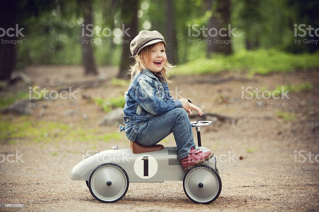 Girl with pedal car stock photo