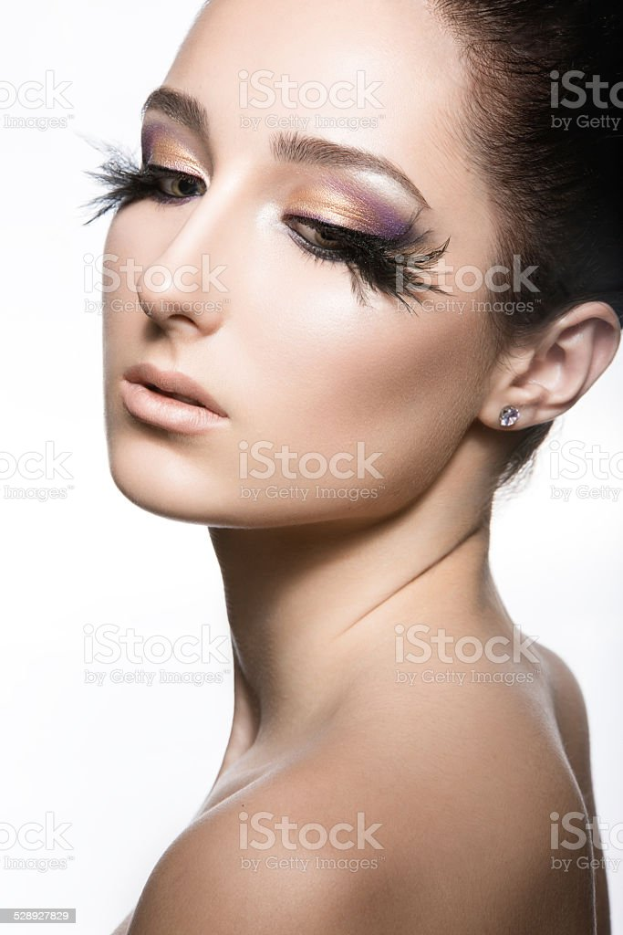 Girl with perfect skin and unusual makeup with feathers. stock photo