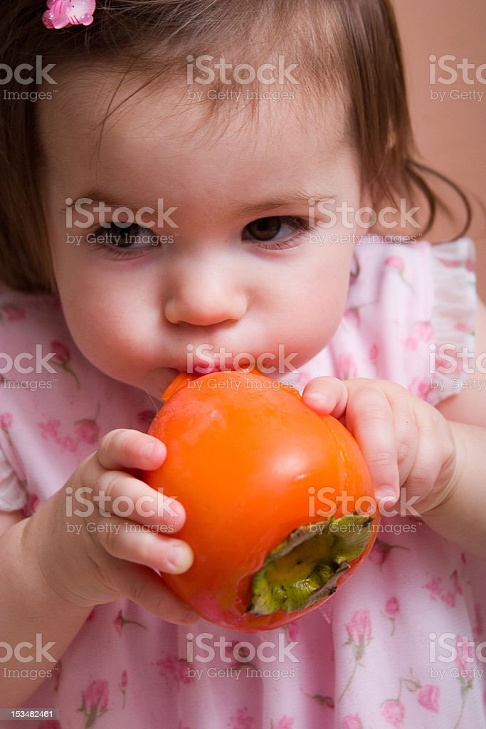 girl with persimmon royalty-free stock photo