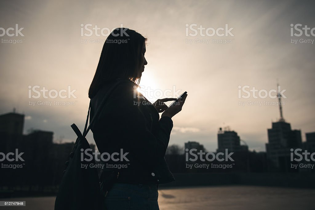 Girl with phone on evening city background stock photo
