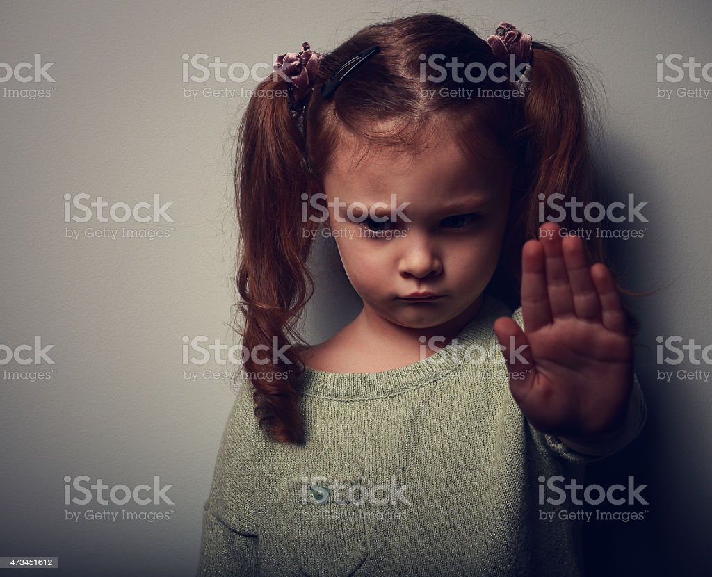 Girl with pigtails in shadow with hand up in stop gesture stock photo
