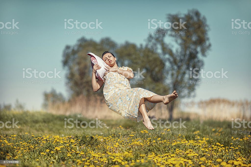 Girl with pillow soars. stock photo