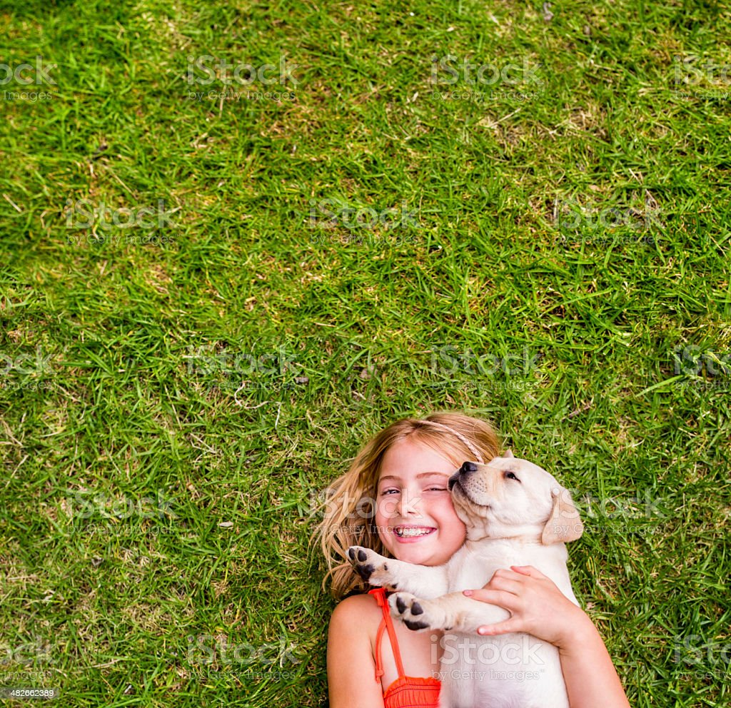 Girl with puppy lying on grass stock photo