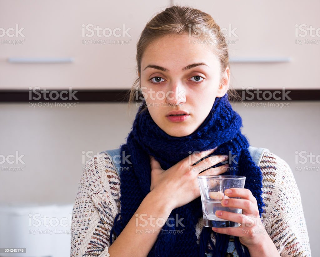 Girl with quinsy taking medicine stock photo