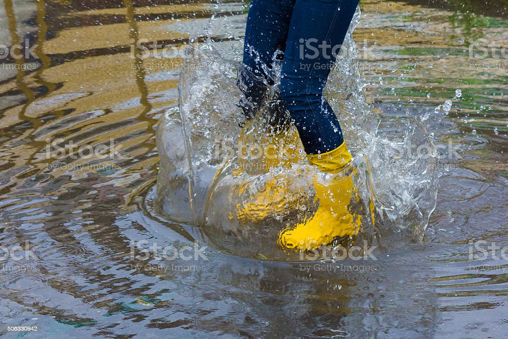 Girl with rain boots jumps into a puddle stock photo