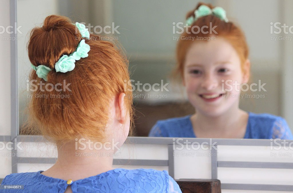 Girl with red hair in bun, looking in mirror, posing stock photo