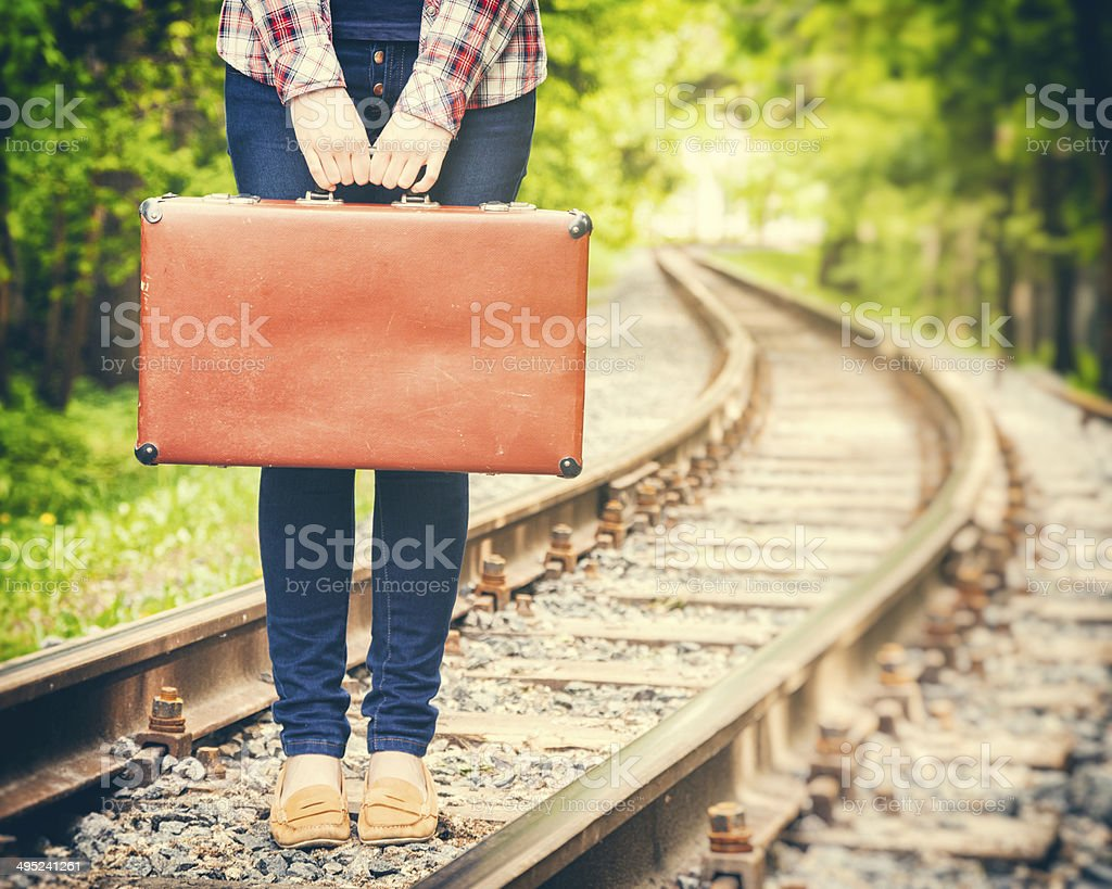 girl with retro suitcase on railway stock photo