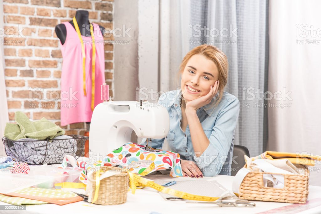 Girl with sewing machine stock photo
