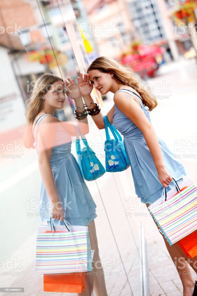 Girl with shopping bags looking through shop window royalty-free stock photo