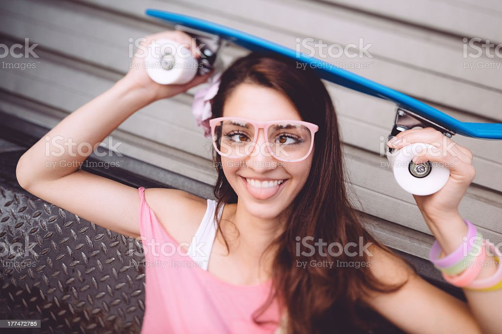 Girl with skateboard making a face royalty-free stock photo
