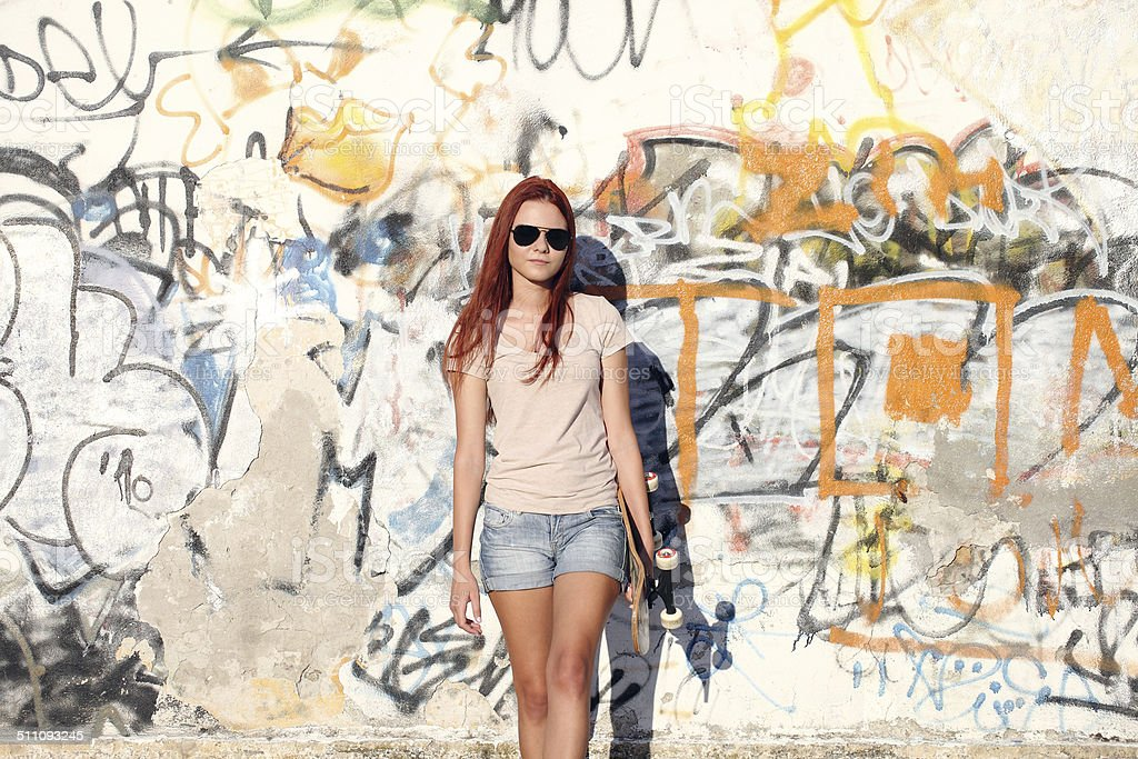 girl with skateboard on background of graffiti stock photo