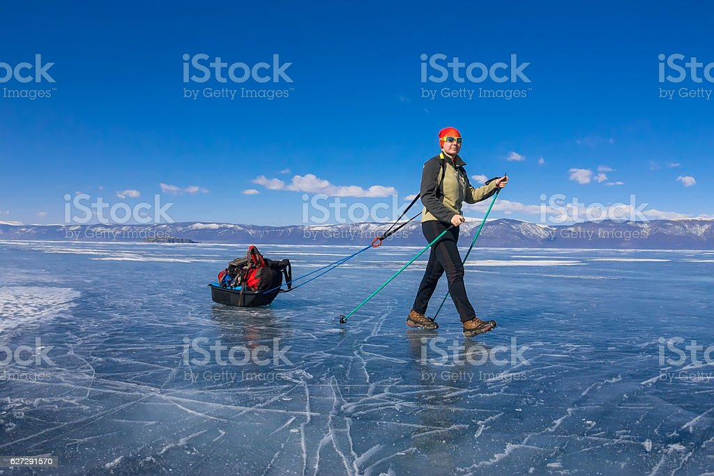Girl with sledge and trekking pole on ice of Baikal stock photo