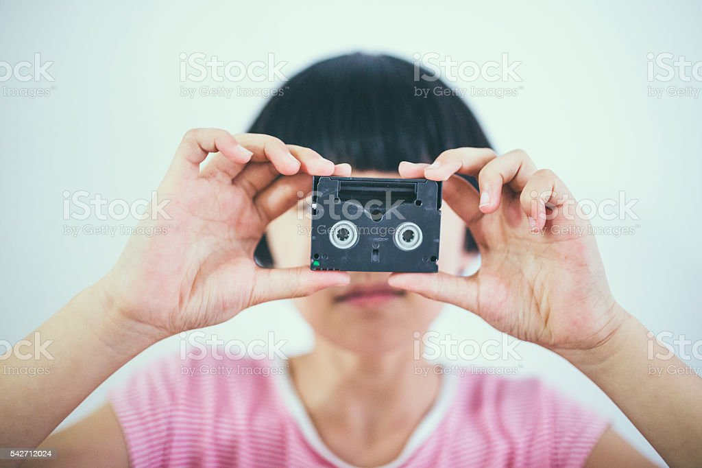 girl with small video tape in mouth stock photo
