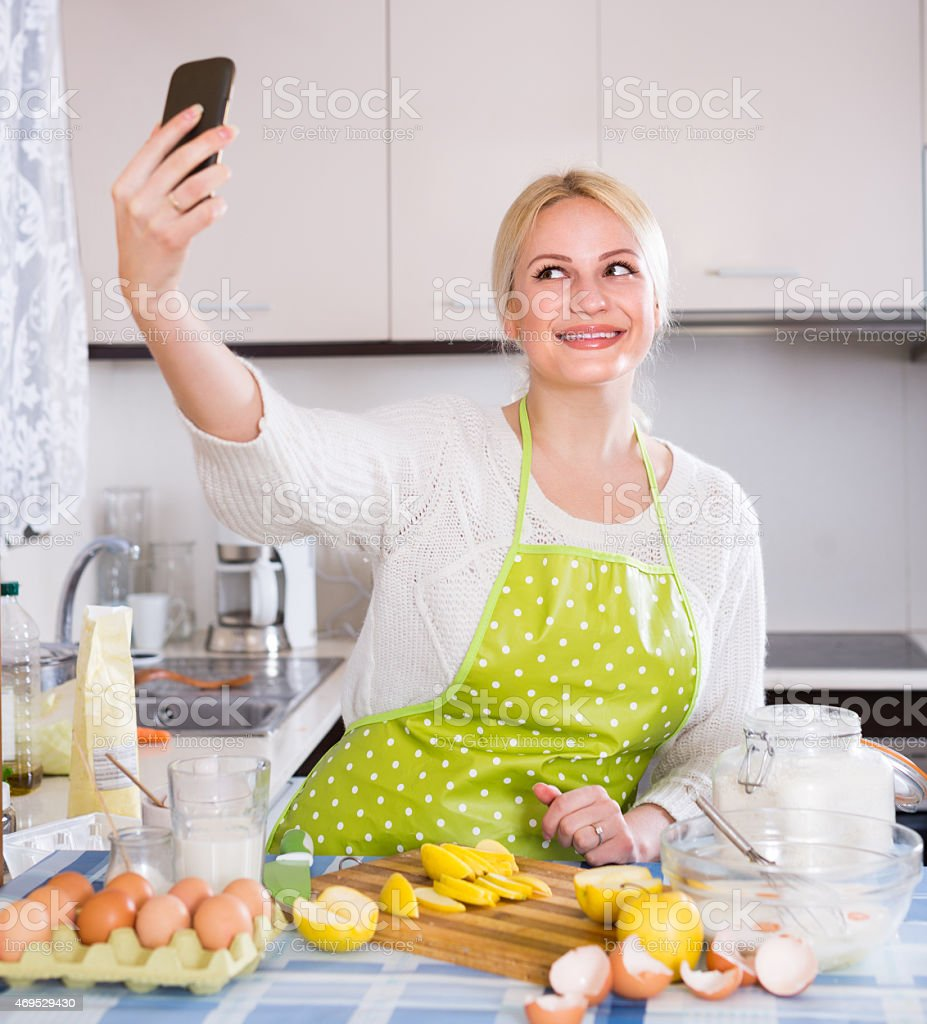 Girl with smartphone at kitchen stock photo