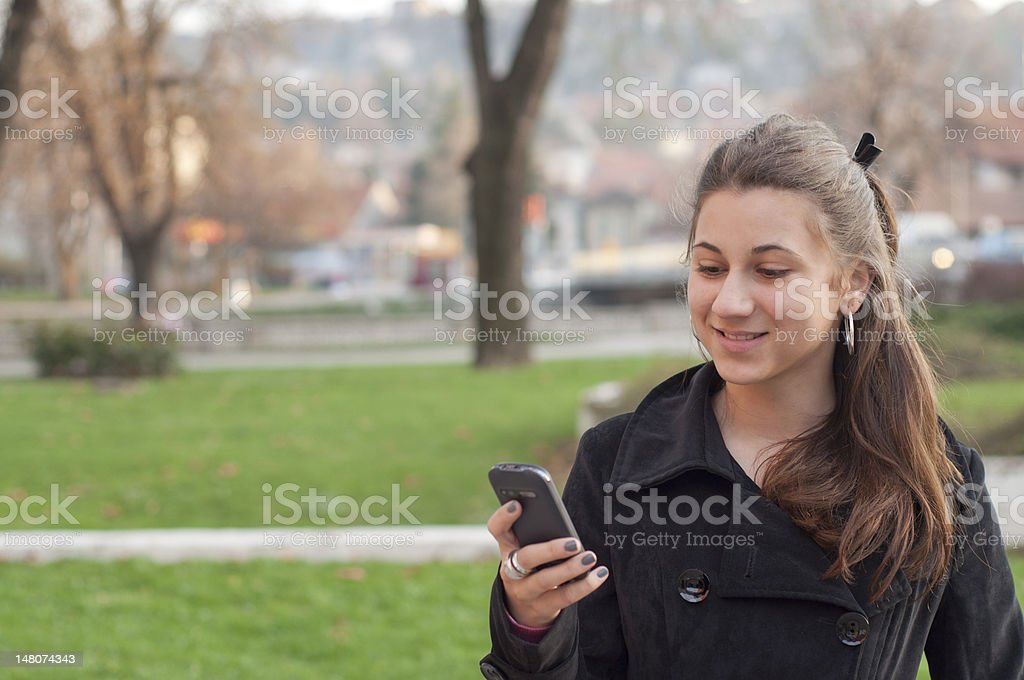 Girl with smartphone in urban enviroment royalty-free stock photo