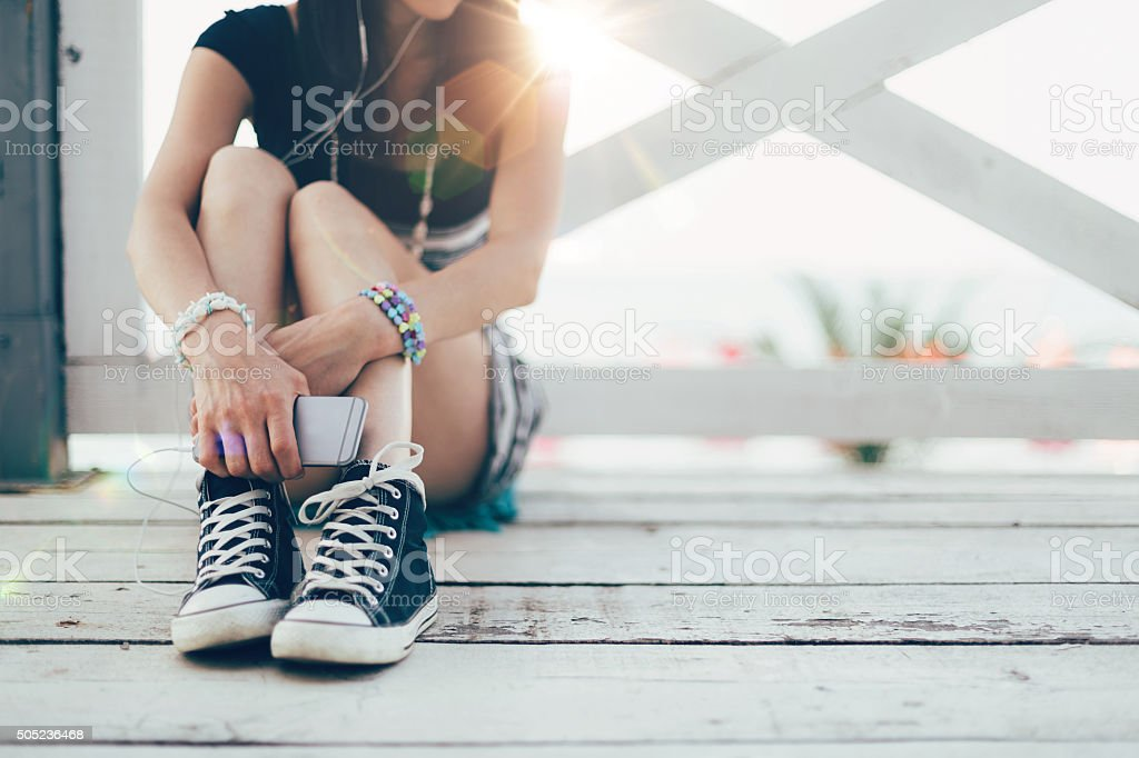 Girl with smartphone sitting at a veranda on the beach stock photo
