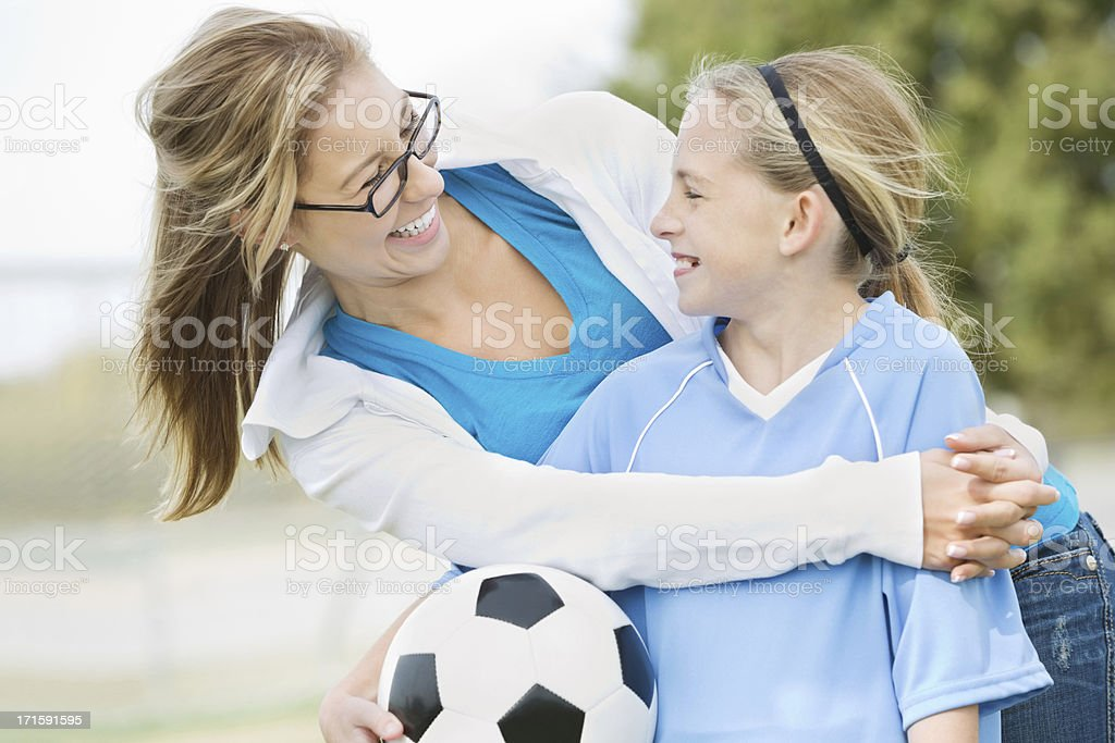 Girl with soccer ball embraced and smiling with older woman. stock photo