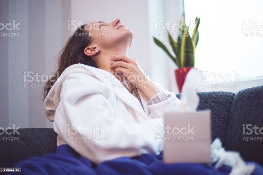 Girl with sore throat ,holding her neck stock photo