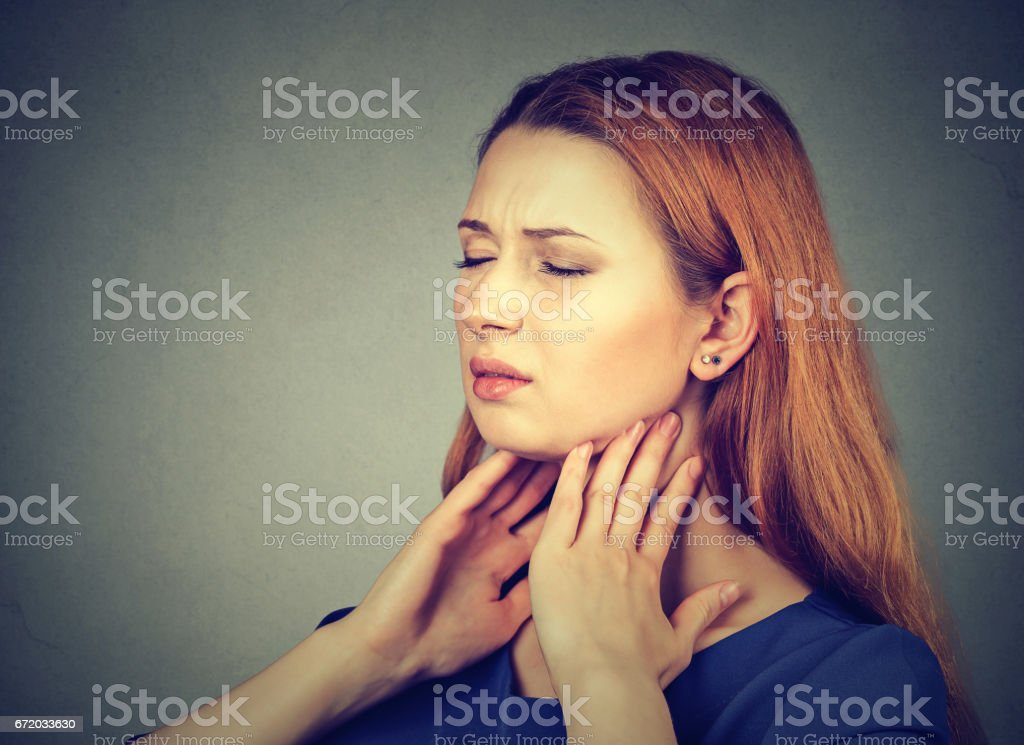 girl with sore throat touching her neck. Sick young woman having pain in her throat stock photo
