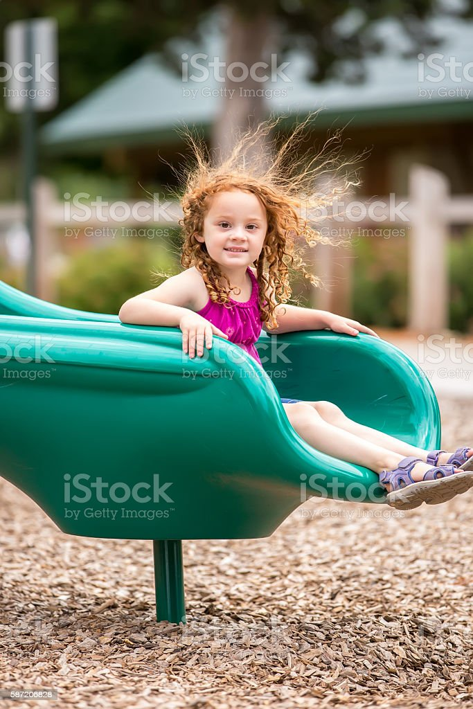 Girl With Static Hair Sticking Up At Playground stock photo