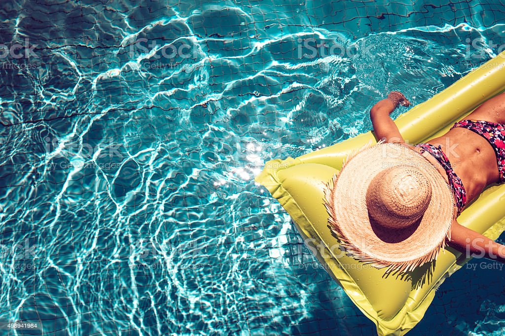 girl with straw hat on airbed swimming in blue pool stock photo