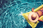 girl with straw hat on airbed swimming in blue pool