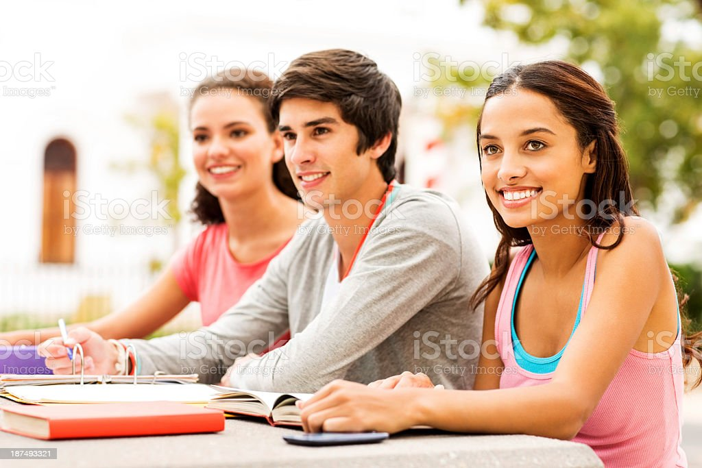 Girl With Students Sitting At Table On College Campus royalty-free stock photo