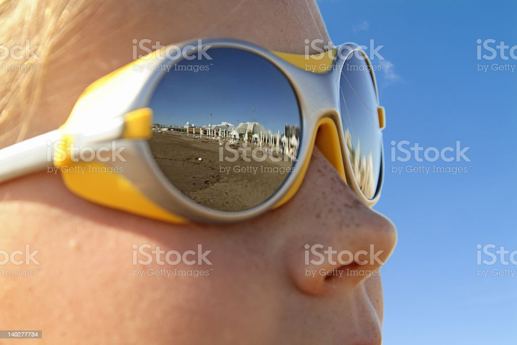 girl with sunglasses (reflecting the beach) and coastline) stock photo