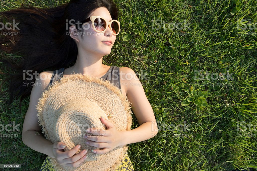 Girl with sunglasses to rest in a field. stock photo