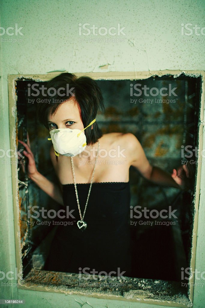 Girl with Surgical Mask in Broken Window royalty-free stock photo
