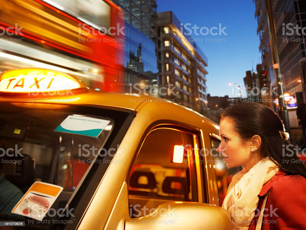 Girl with taxi in London by night stock photo