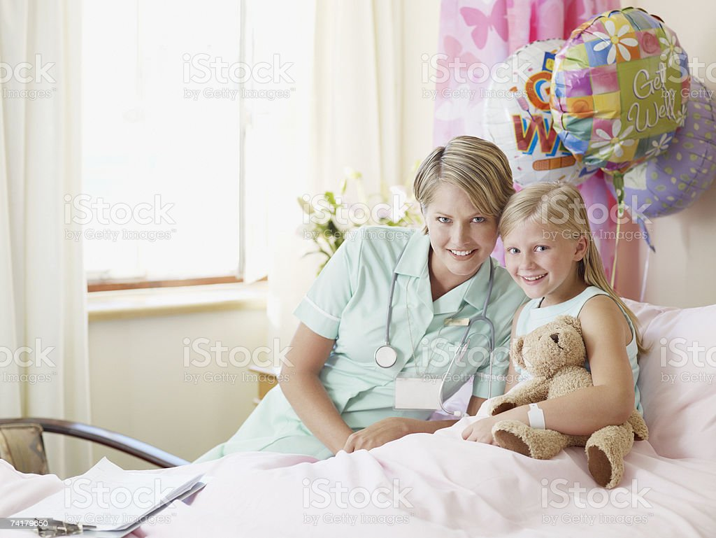 Girl with teddy bear and nurse in hospital royalty-free stock photo