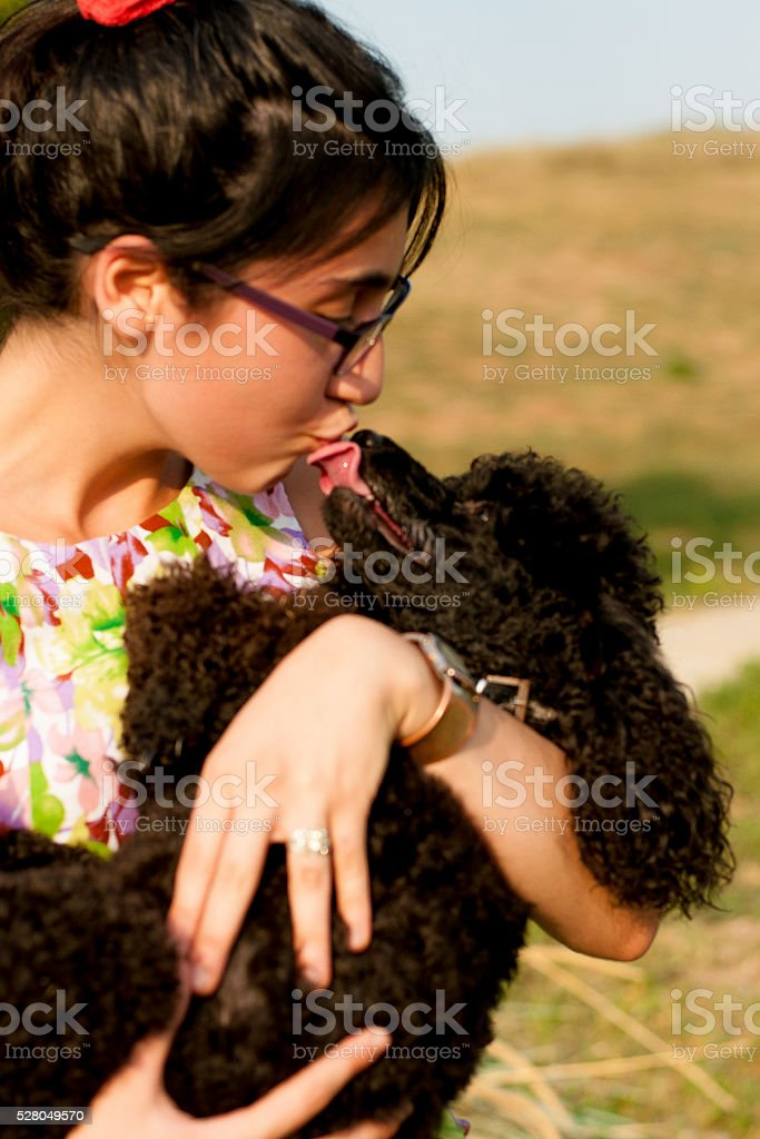 Girl with the black poodle on nature stock photo