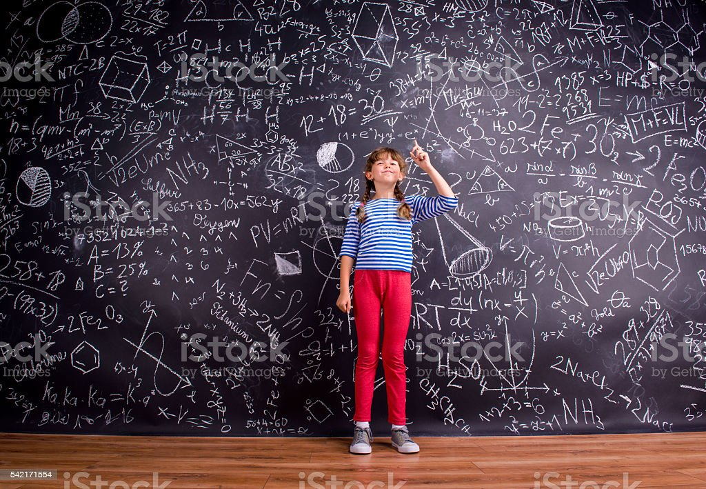 Girl with two braids, big blackboard with mathematical symbols stock photo