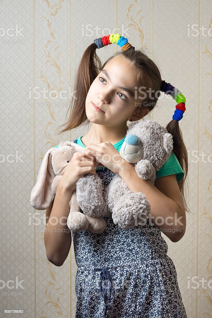 girl with two soft toys dreamily nostalgic looking up. stock photo