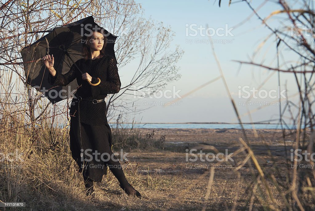 girl with umbrella on background of trees and the beach stock photo